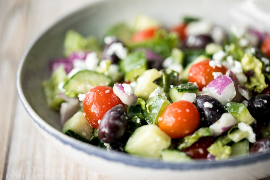 The perfect Greek salad with fresh tomatoes, cucumbers, red onions, green peppers, romaine lettuce, olives and feta cheese tossed in a lemon vinaigrette. | aheadofthyme.com