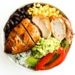It's time for a fiesta with chipotle chicken burrito bowls served with lime cilantro rice, sautéed bell peppers, corn, black beans and guacamole. | aheadofthyme.com