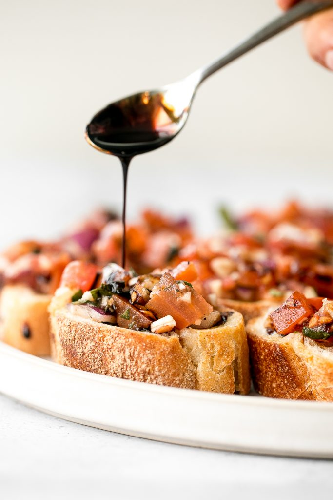 Tomato bruschetta with balsamic glaze is an easy Italian appetizer topped with tomatoes, onions, garlic, basil and olive oil. Delicious, fresh and simple. | aheadofthyme.com