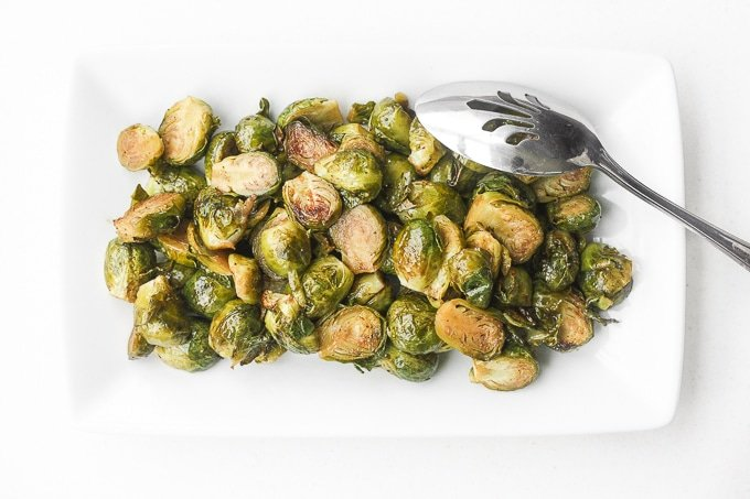Easy Roasted Brussels Sprouts: Tender and caramelized, easy roasted brussels sprouts tossed in balsamic vinegar and honey is a classic household favourite to serve on your holiday table. | aheadofthyme.com