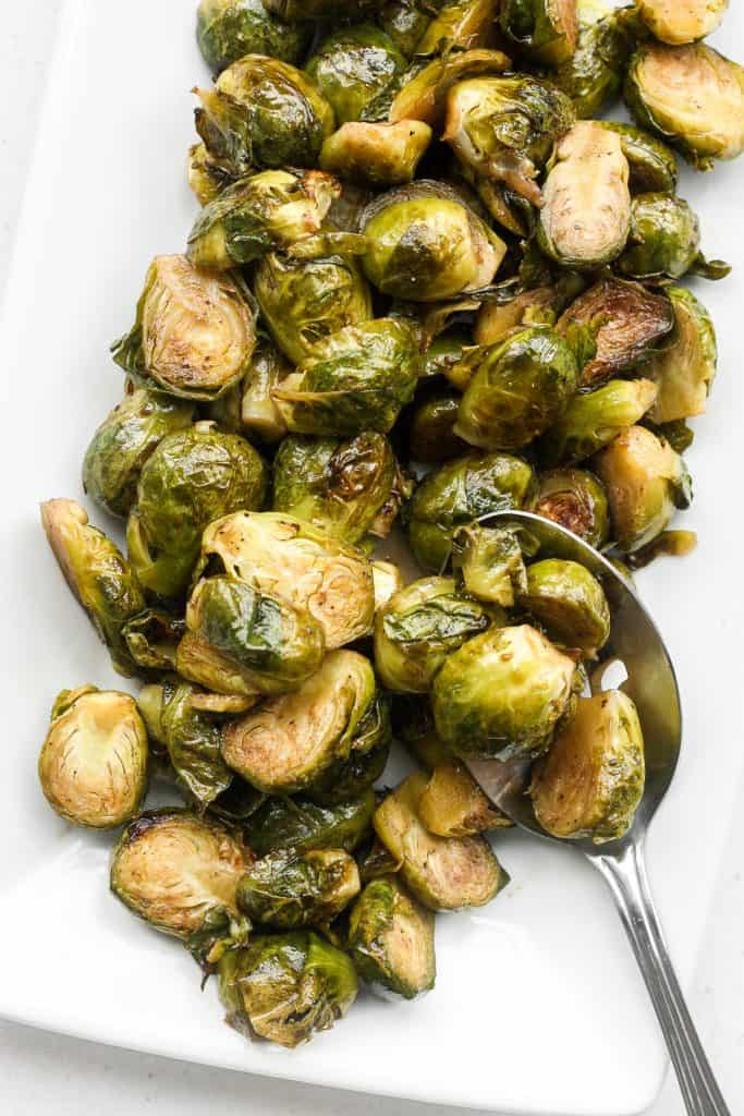 Tender and caramelized, easy roasted brussels sprouts tossed in balsamic vinegar and honey is a classic household favourite to serve on your holiday table. | aheadofthyme.com