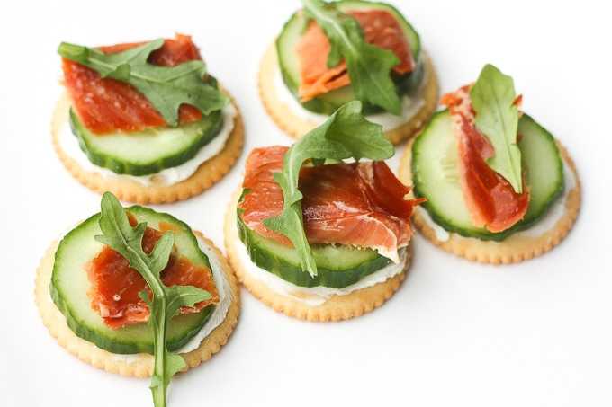 Smoked salmon and cream cheese cracker bites are topped with cucumber and arugula to make the perfect bite-size snacks. | aheadofthyme.com