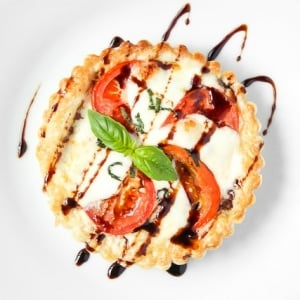 Looking for the perfect appetizer or light lunch? Try a tomato and mozzarella tart topped with basil and a drizzle of pomegranate molasses! | aheadofthyme.com