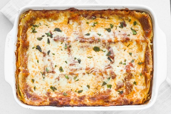 Take comfort food to another level with the best creamy spinach and tomato vegetarian lasagna. You won't even miss the meat! | aheadofthyme.com