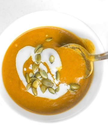Coconut curry pumpkin soup is a bowl of comfort with a kick. This soup comes together in less than 30 minutes using a handful of ingredients!   aheadofthyme.com
