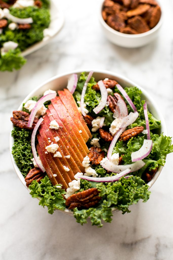 Cozy winter kale salad with apple cider vinaigrette is easy to make with crispy apples, tangy goat cheese and crunchy spiced pecans in under 10 minutes. | aheadofthyme.com