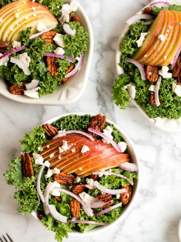 Cozy winter kale salad with apple cider vinaigrette is easy to make with crispy apples, tangy goat cheese and crunchy spiced pecans in under 10 minutes.   aheadofthyme.com