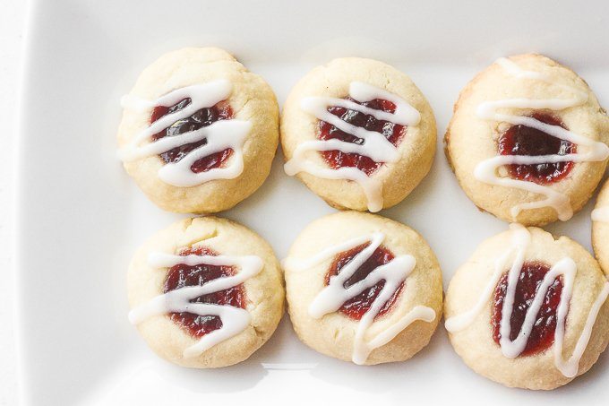 Soft, buttery, melt-in-your mouth jam-filled thumbprint cookies with almond glaze are the cutest, festive treat to make. | aheadofthyme.com
