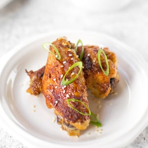 You will be amazed by how crispy these baked Asian chicken wings turn out! We add sriracha for heat, honey for sweetness, and ginger to balance the flavours. | aheadofthyme.com