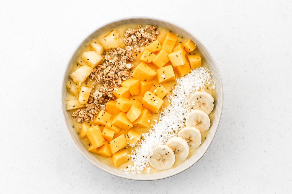 Mango pineapple tropical smoothie bowl? Yes, please! Who doesn't love pineapples and mangos blended together and topped with more fruit, granola, and coconut? | aheadofthyme.com