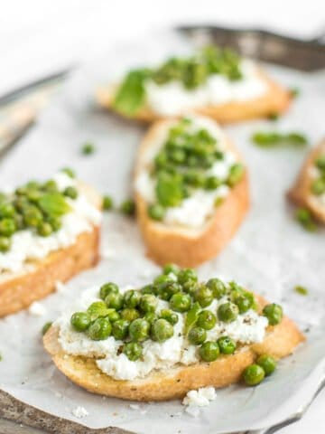 Get ready for spring with this impressive appetizer, crostini with ricotta, peas and mint! The way creamy ricotta pairs with fresh English peas and mint is unparalleled! Trust me, SO delicious.| aheadofthyme.com