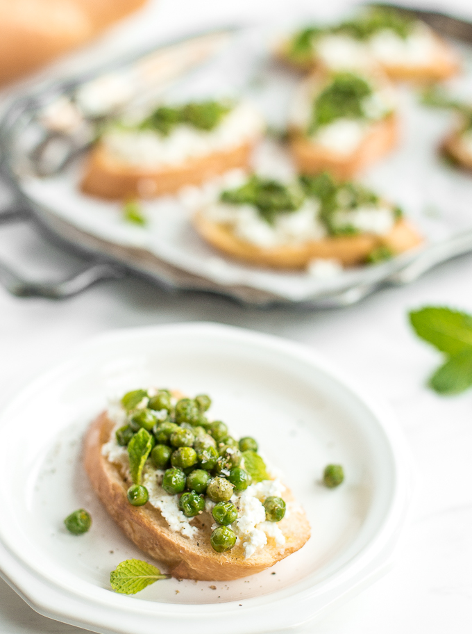 Get ready for spring with this impressive appetizer, crostini with ricotta, peas and mint! The way creamy ricotta pairs with fresh English peas and mint is unparalleled! Trust me, SO delicious. | aheadofthyme.com