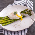 Roasted asparagus with poached eggs is a match made in food heaven. Serve this topped with fresh herbs and lots of black pepper for a classy, elevated brunch dish that will leave you feeling light, but completely satisfied, or simply to celebrate the arrival of spring! | aheadofthyme.com