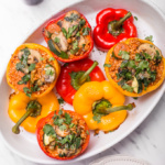 Fresh, homegrown bell peppers baked with an assortment of veggies and brown rice is what these easy vegan stuffed bell peppers are all about!! Ready in under an hour, serve this at your next fancy dinner party or make it for an easy weeknight dinner! | aheadofthyme.com