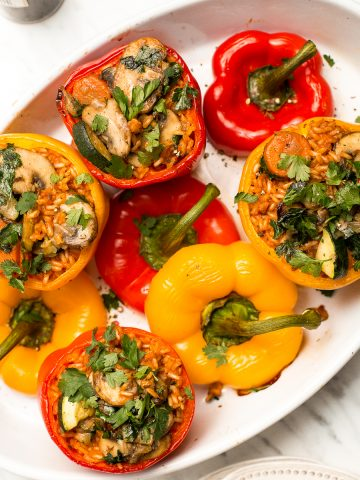 Easy vegan stuffed bell peppers are filled with brown rice, mushrooms, veggies, and seasonings, then baked for 40 minutes. It's a perfect weeknight dinner.   aheadofthyme.com