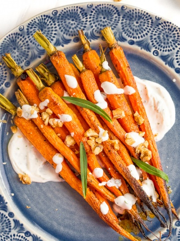 These maple roasted carrots with yogurt sauce are not only stunning, but they get all caramelized and crispy around the sides from the maple syrup... pure perfection!   aheadofthyme.com