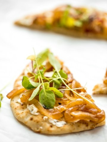 Crispy flatbread, warm, melty goat cheese with garlic and herbs, and mounds of sweet onion. You seriously cannot go wrong with caramelized onion and herbed goat cheese flatbread. | aheadofthyme.com