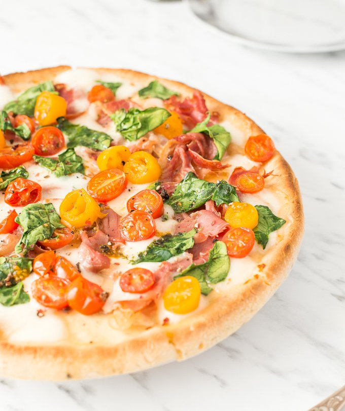 The combination of salty prosciutto, sweet tomatoes, gooey mozzarella and delicate spinach to come together to create a masterpiece -- spinach tomato and prosciutto pizza! | aheadofthyme.com
