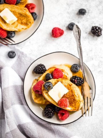 Triple berry french toast with warm slices of bread, creamy egg mixture, an overload of berries, and maple syrup drizzled on top is breakfast goals.   aheadofthyme.com