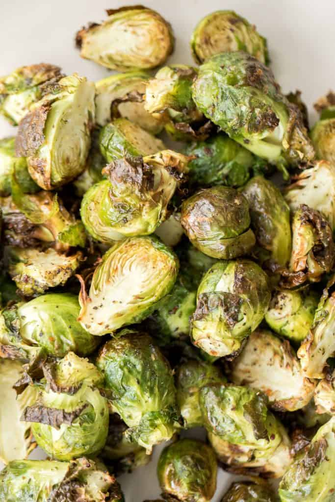 Tender and crispy roasted air fryer brussels sprouts cooks in less than 12 minutes with very little oil. It is a holiday table game changer. | aheadofthyme.com