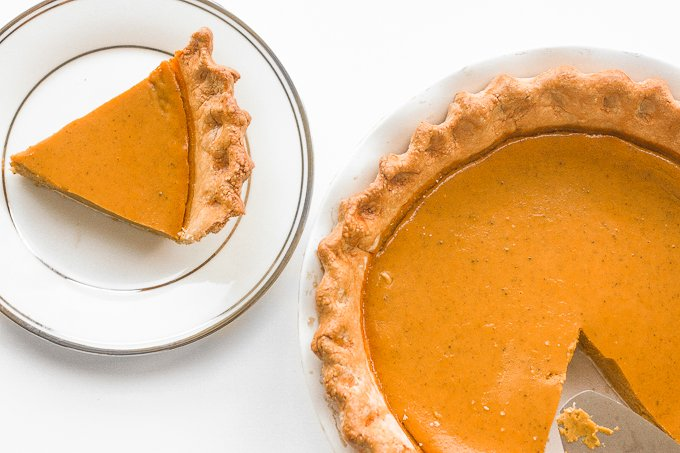 Thanksgiving just isn't the same without a slice of classic Thanksgiving pumpkin pie with flaky crust, smooth pumpkin filling, and topped with whipped cream and pecans. | aheadofthyme.com