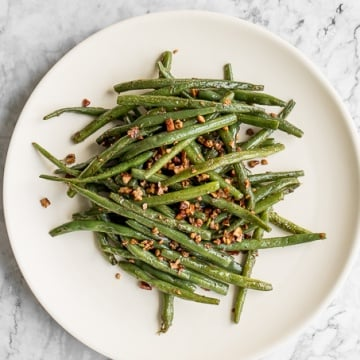 With only a few ingredients, it is amazing how much flavour these 10-minute nutty green beans produce. Earthy green beans perfectly balance with crunchy pecans, and coated with smooth buttery goodness. | aheadofthyme.com