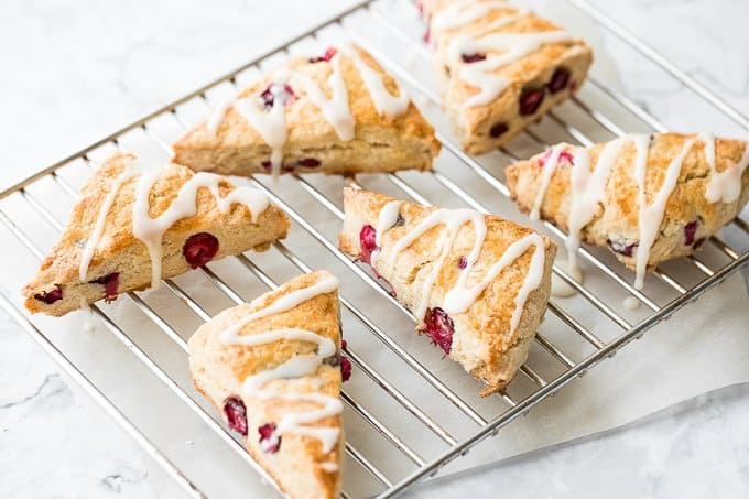 A light, tender and flakey cranberry scone, drizzled with a sweet orange glaze is the perfect winter breakfast. | aheadofthyme.com