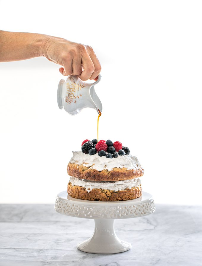 This healthy banana smash cake is held together with a whipped coconut cream frosting and topped with more cream, mixed berries and a drizzle of maple syrup. | aheadofthyme.com