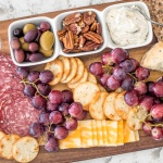 Take your party to another level with this easy to follow guide on how to make a charcuterie board, with a variety of cheese, cured meats, crackers, olives and dips. | aheadofthyme.com