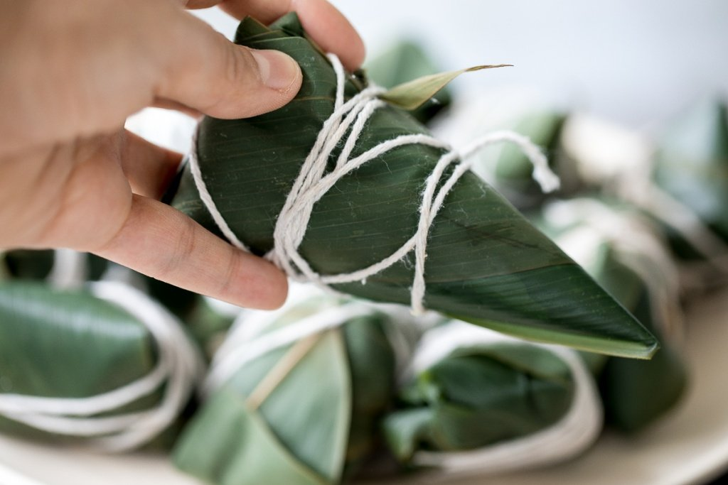 Zongzi Chinese tamales (粽子) or sticky rice dumplings are stuffed with sticky rice, pork belly, and shiitake mushrooms, wrapped inside reed or bamboo leaves. | aheadofthyme.com