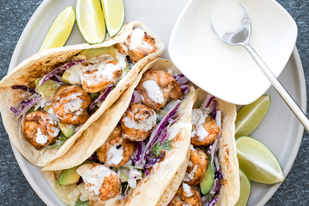 Quick and easy shrimp tacos with lime crema slaw are ready in less than 30 minutes and are packed with flavourful crispy shrimp and creamy cabbage slaw. | aheadofthyme.com