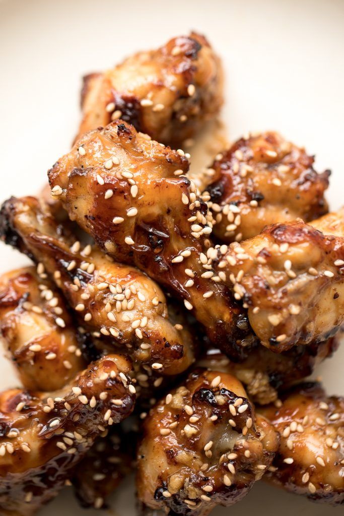 These sweet and sticky honey garlic chicken wings are baked or air fried until crispy and tossed in a honey garlic sauce. So addictive and so easy to make. | aheadofthyme.com