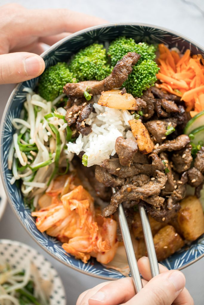 Korean beef steak rice bowl is loaded with tender and juicy strips of beef, marinated vegetable sides (banchan), and kimchi. Make it in under 30 minutes! | aheadofthyme.com
