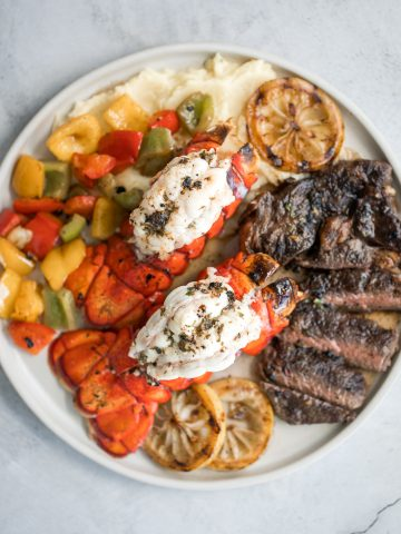 Fancy, restaurant-quality surf and turf is super easy to make with fresh lobster tail and tender rib-eye steak with a delicious garlic butter sauce. | aheadofthyme.com