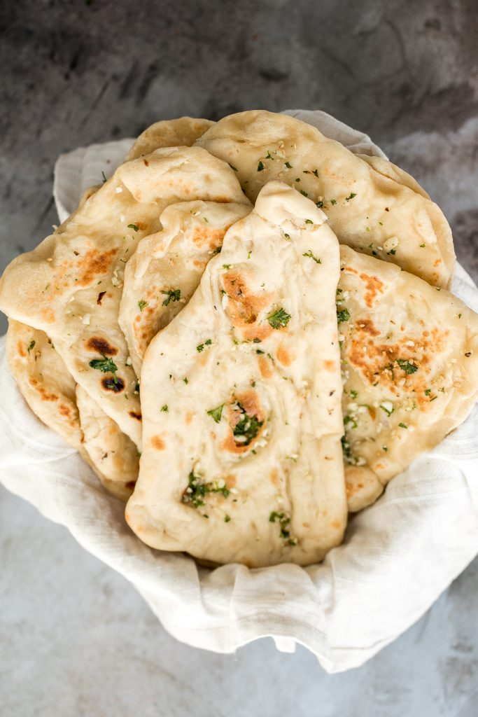Freshly baked small batch garlic naan bread is buttery, garlicky, soft and pillowy, and full of perfect blistered air pockets. It's quick and easy to make. | aheadofthyme.com