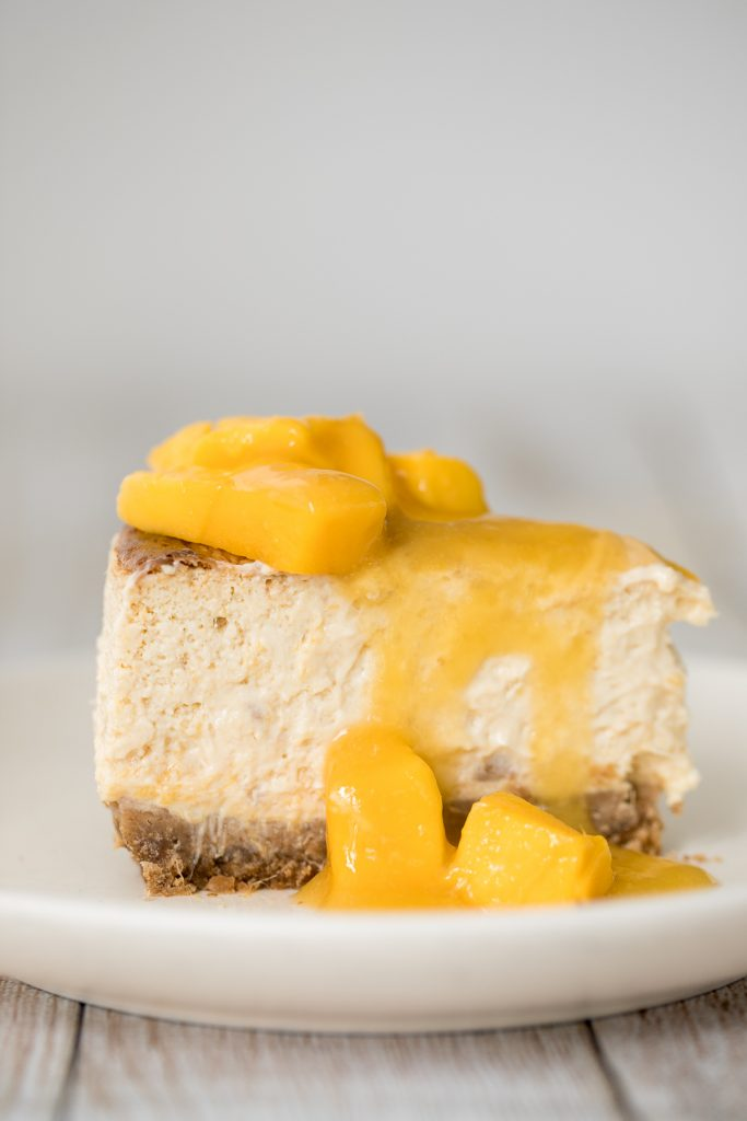 Mousse-like, creamy mango cheesecake with a graham cracker crust, light cheesecake filling packed with mangos, and mango swirled on top is so easy to make. | aheadofthyme.com
