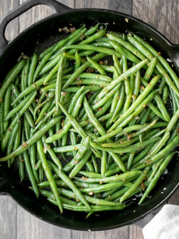 Buttery sautéed garlic green beans is a simple side dish that is quick, easy and delicious. Make these vibrant, crispy and tender green beans in 10 minutes.   aheadofthyme.com