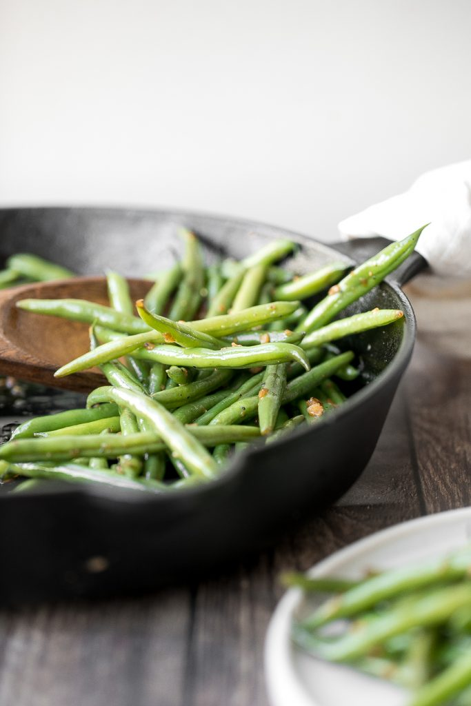 Buttery sautéed garlic green beans is a simple side dish that is quick, easy and delicious. Make these vibrant, crispy and tender green beans in 10 minutes. | aheadofthyme.com