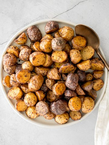 Crispy and tender, easy air fryer baby potatoes are a healthier take on a classic side dish without compromising taste or texture. Cooks in just 20 minutes.   aheadofthyme.com