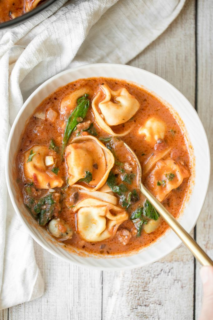 Hearty and creamy tortellini soup with sausage, spinach and kale is total comfort food in a bowl. Make this flavourful one pot meal in under 30 minutes. | aheadofthyme.com