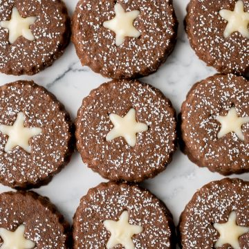 Soft and warmly spiced gingerbread linzer cookies with white chocolate ganache and dusted with confectioners' sugar is a delicious Christmas holiday cookie. | aheadofthyme.com