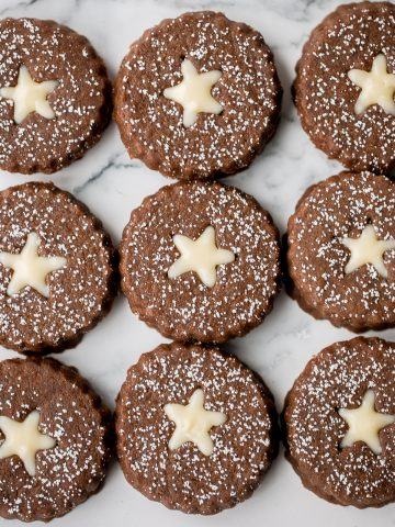 Soft and warmly spiced gingerbread linzer cookies with white chocolate ganache and dusted with confectioners' sugar is a delicious Christmas holiday cookie.   aheadofthyme.com
