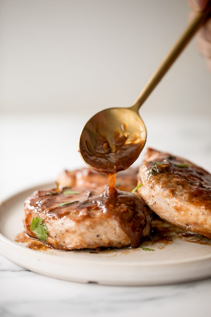 Quick and easy, glazed honey balsamic pork chops are tender and juicy, seared in thyme and coated with a honey balsamic sauce. Make it in under 30 minutes. | aheadofthyme.com