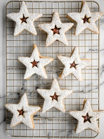 Sweet buttery linzer cookies are a classic Christmas cookie with flaky shortbread and fruit jam. The perfect festive holiday treat that melts in your mouth.   aheadofthyme.com