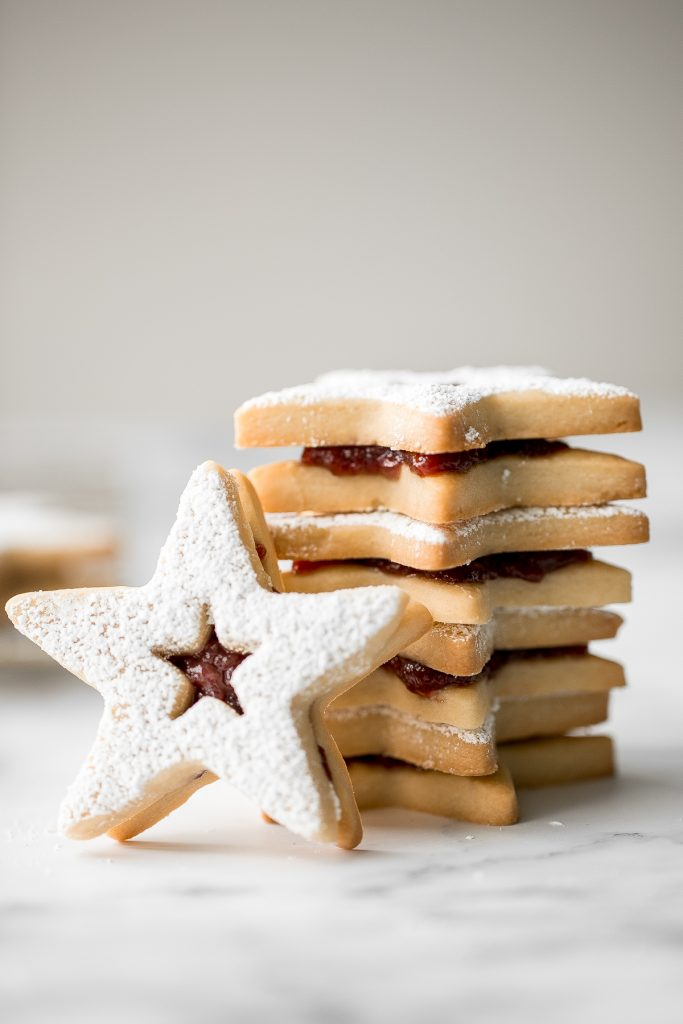 Sweet buttery linzer cookies are a classic Christmas cookie with flaky shortbread and fruit jam. The perfect festive holiday treat that melts in your mouth. | aheadofthyme.com