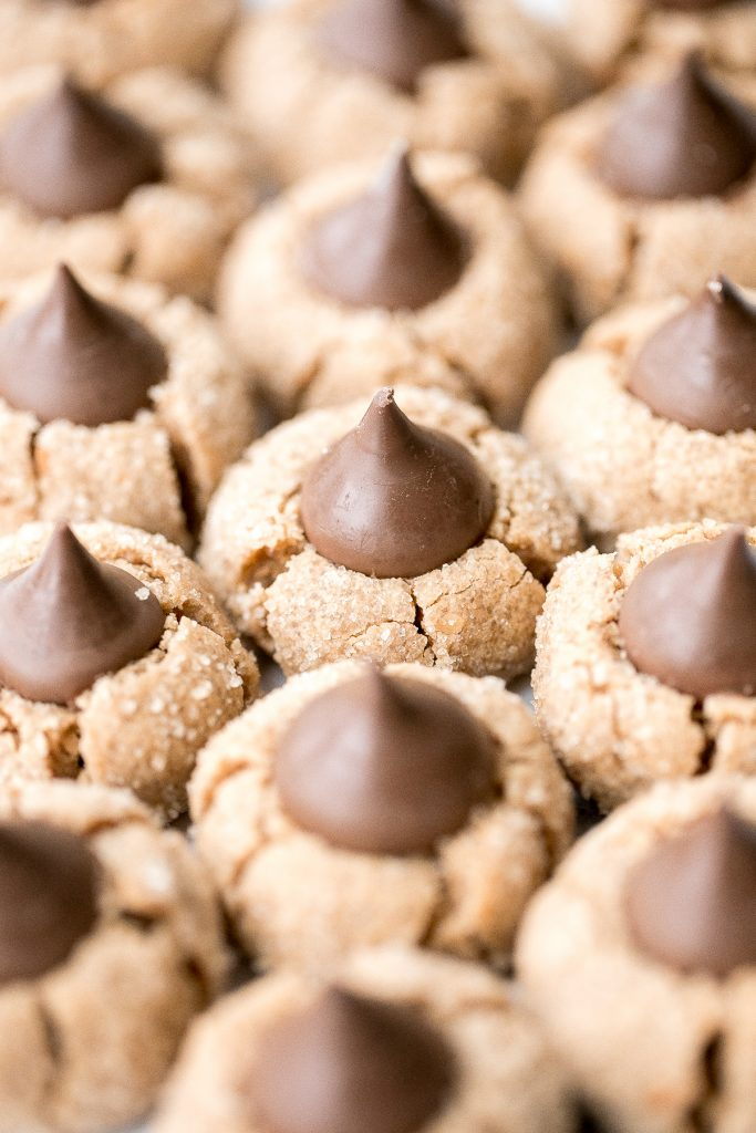 Soft chewy peanut butter blossoms topped with a chocolate kiss are a classic Christmas cookie that is easy to make during the holidays or any time of year. | aheadofthyme.com