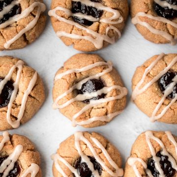 Melt-in-your-mouth peanut butter thumbprint cookies with raspberry jam and a drizzle of maple cinnamon glaze are the best holiday cookies and easy to make. | aheadofthyme.com