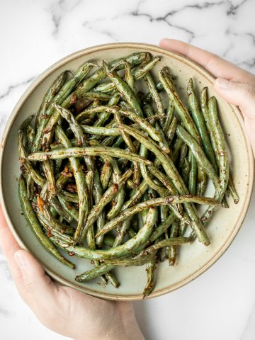 Quick easy roasted garlic green beans are tangy, sour, savoury, and sweet, with a tender and crunchy texture. Make them in the oven or air fryer in minutes.   aheadofthyme.com