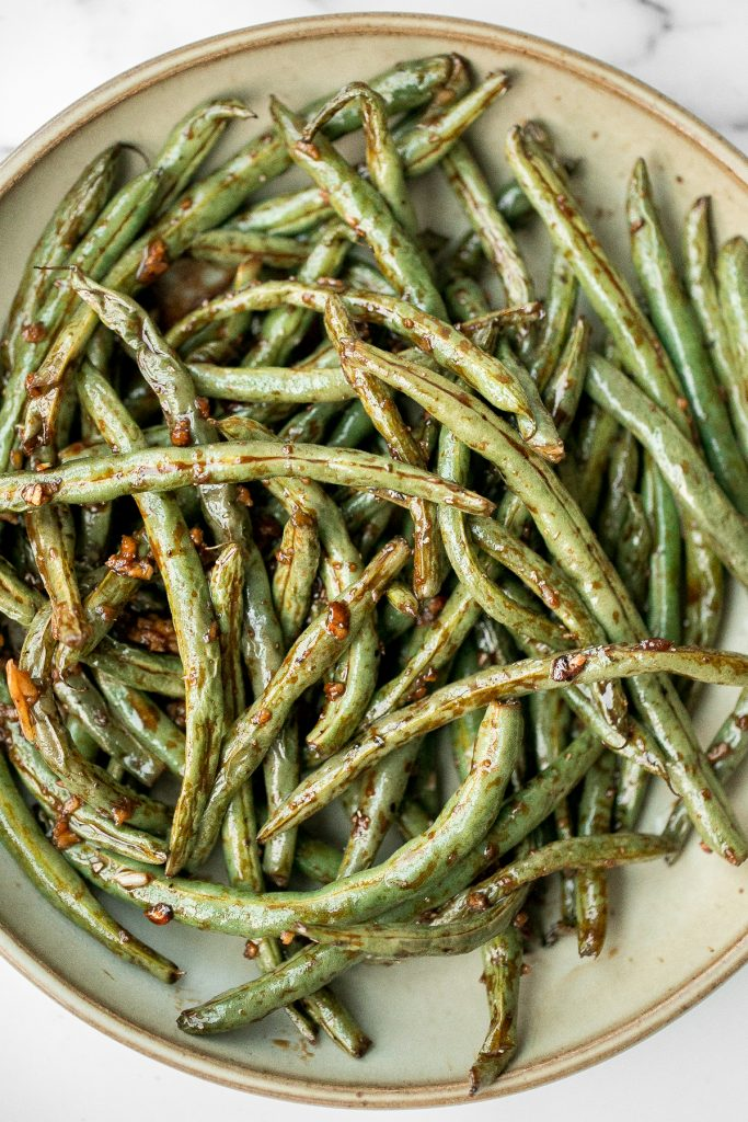 Quick easy roasted garlic green beans are tangy, sour, savoury, and sweet, with a tender and crunchy texture. Make them in the oven or air fryer in minutes. | aheadofthyme.com