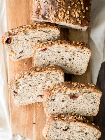 Whole wheat cranberry bread is chewy, fluffy and airy, packed with dried cranberries and seeds, and has a perfect crunchy crust topped with oats and seeds.   aheadofthyme.com